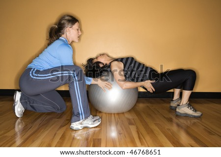 Woman steadies a balance ball for another woman lying back on it at the gym. Horizontal shot. - stock photo