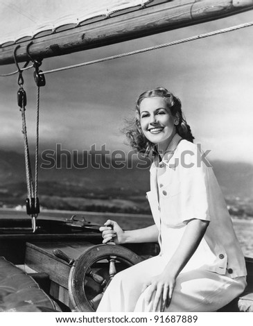 Woman steering sailboat - stock photo