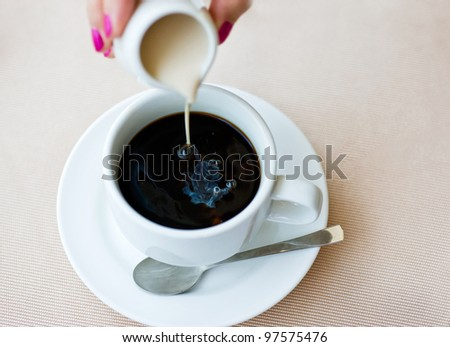 Woman stirring a cup of coffee - stock photo