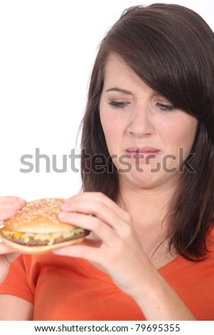 Woman stood holding cheeseburger - stock photo