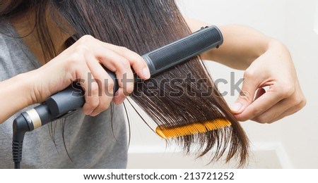 Woman straightening hair with straightener on right hand and comb on left hand. - stock photo