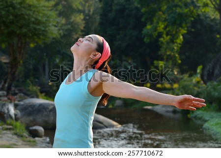 Woman stretching her arms to enjoy the fresh air in the park - stock photo