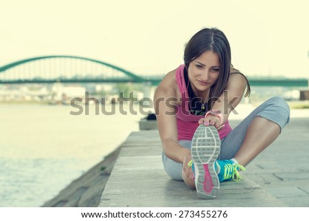 Woman stretching her leg by the river after running... - stock photo
