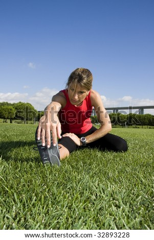 Woman stretching her leg on the park - stock photo