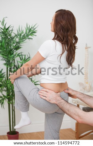 Woman stretching her leg while a man is touching her back in a room
