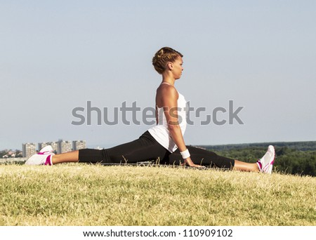 Woman stretching. Open door shot. On an early morning sun. - stock photo