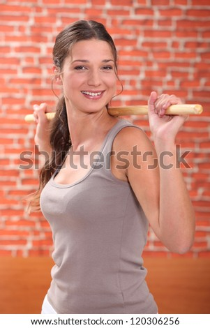 Woman stretching with wooden pole - stock photo