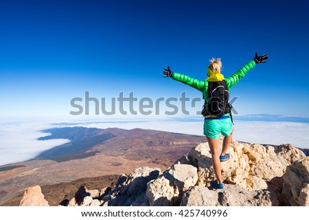Woman successful hiking climbing in mountains, motivation and inspirational landscape on island and ocean. Hiker with arms up outstretched on mountain top looking at beautiful view on Tenerfie, Spain. - stock photo