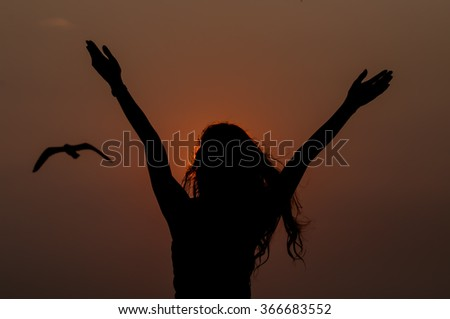woman successfull and very happy open arms under the sunset