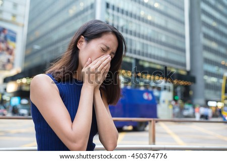 Woman suffer from nose allergy due to air pollution - stock photo