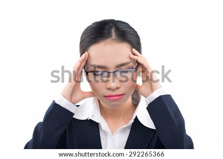 Woman suffering from a migraine headache rubbing her temples with her fingers and grimacing in pain, studio portrait isolated on white background. Asian female model. - stock photo
