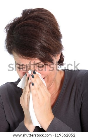 Woman suffering from a seasonal winter cold and flu sneezing and blowing her nose on a handkerchief, head and shoulders studio portrait on white - stock photo