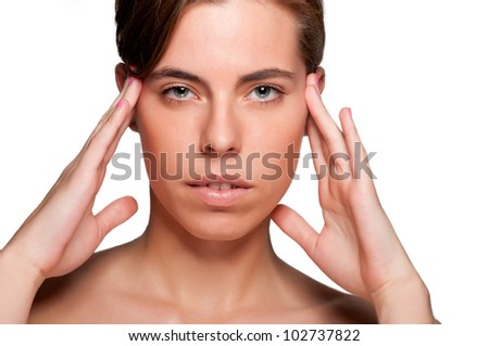 Woman suffering from an headache, holding her hands to the head - stock photo