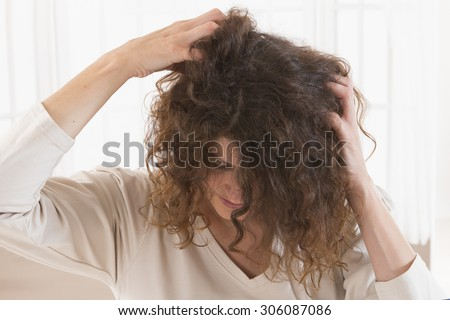Woman suffering from an headache itching her head - stock photo