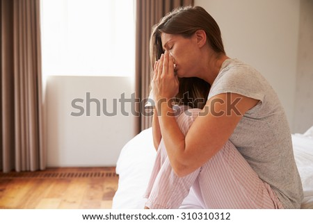 Woman Suffering From Cold Sitting On Bed With Tissue