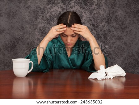 Woman suffering from headache and flu symptoms at home with a coffee cup and tissues - stock photo