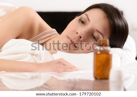 Woman suffering from illness or insomnia lying in bed eying a bottle of medication and displayed tablets with a frown as she debates the advantage of taking them