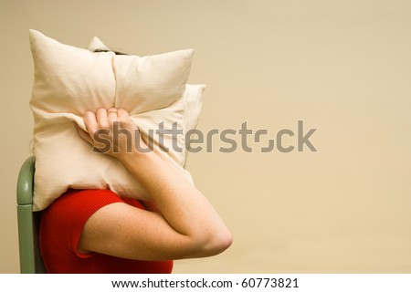 woman suffering from noise and covering her head with a pillow  irritated female lying closing ears with pillow - stock photo