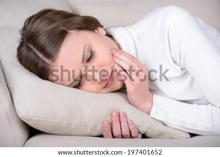 Woman suffering from toothache. Frustrated young woman touching her cheek and looking at camera while standing isolated on white - stock photo