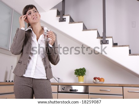 Woman suffering indoor of migraine headache pain in kitchen - stock photo