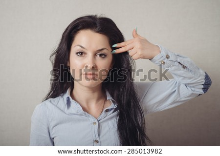 Woman suicide gesture, finger to her temple imitates gun. On a gray background. - stock photo