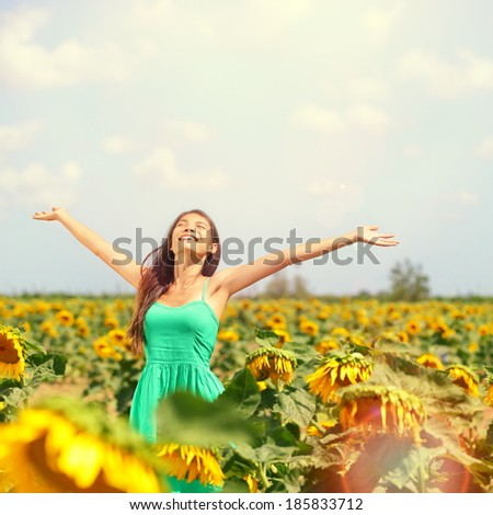 Woman summer girl happy in sunflower flower field. Cheerful multiracial Asian Caucasian young woman joyful, smiling with arms raised up. - stock photo