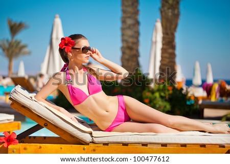 Woman sunbathing in bikini at tropical travel resort. Beautiful young woman lying on sun lounger near pool - stock photo