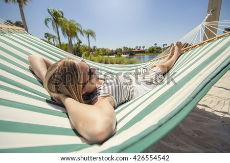 Woman sunbathing, relaxing and resting in a hammock while staying at a tropical resort on vacation - stock photo