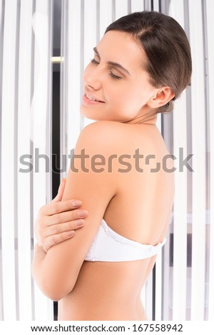 Woman sunbathing. Side view of beautiful young woman standing in tanning booth and keeping eyes closed - stock photo