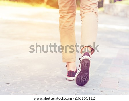 woman sunny walk legs gumshoes - stock photo