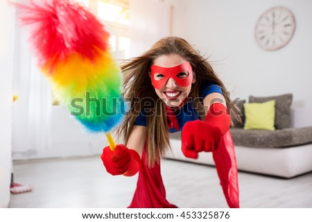 Woman superhero flying through the room with  a feather duster