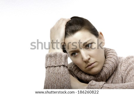 Woman supports head manually with a frustrated expression