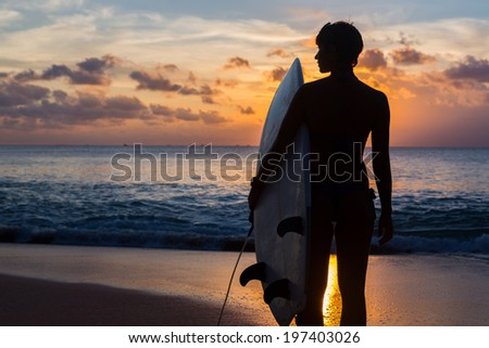 woman surfer with surfboard on tropical beach at sunset - stock photo
