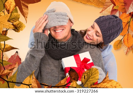 Woman surprising husband with gift against autumn leaves pattern - stock photo