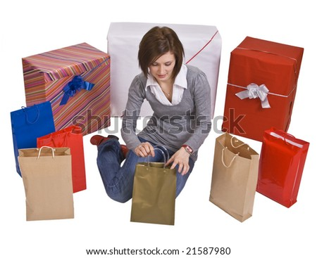 Woman surrounded by a lot of gifts looking in a bag. - stock photo
