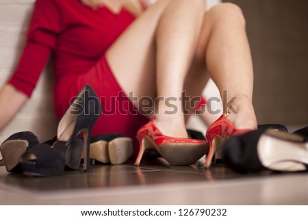 Woman surrounded by  shoes - stock photo