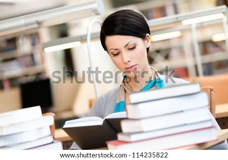 Woman surrounded with piles of books reads sitting at the desk at the library. Academic achievement - stock photo