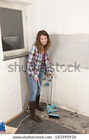 Woman sweeps up dust from the floor