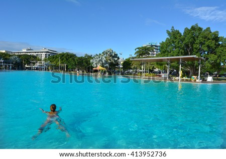 Woman swim in Cairns Esplanade Swimming Lagoon,  a very popular tourist travel destination in Cairns Queensland, Australia. - stock photo