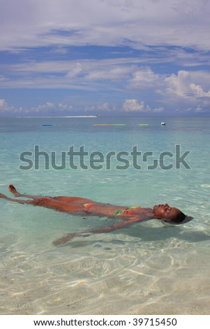 Woman swimming at beach - stock photo