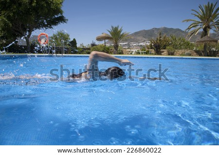 woman swimming crawl in a blue pool