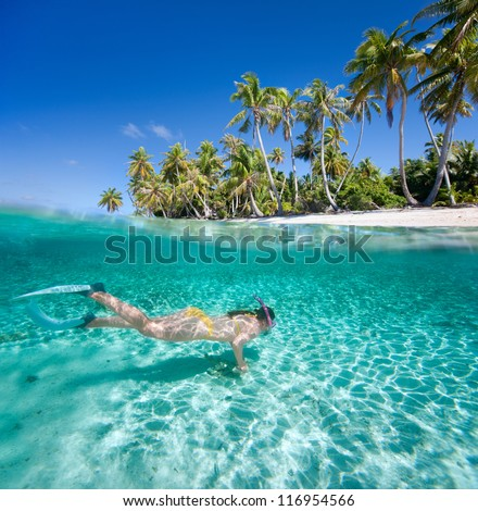 Woman swimming in a clear tropical waters in front of exotic island - stock photo
