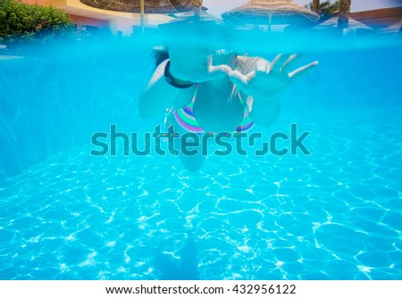 woman swimming in the pool view from under a water