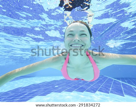 Woman swimming underwater in pool smiling - stock photo