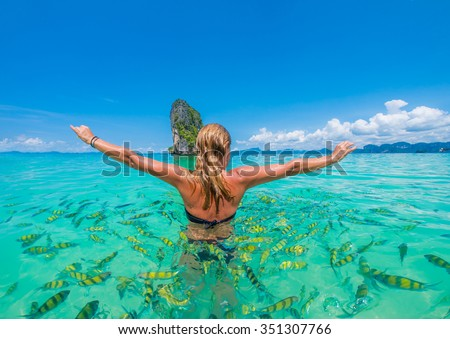 Woman swimming with snorkel surrounded by fish, Andaman Sea, Thailand - stock photo