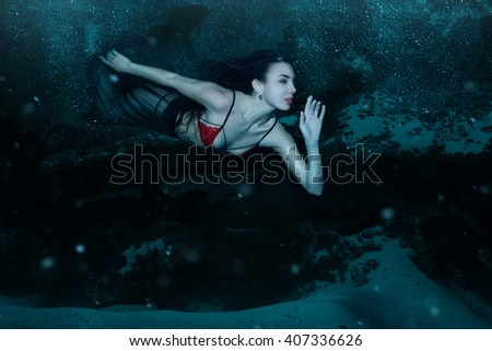 Woman swims like a mermaid at the bottom of the ocean.