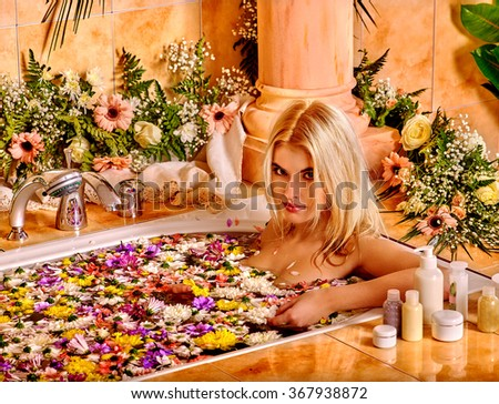 Woman take flower bath in luxury spa.