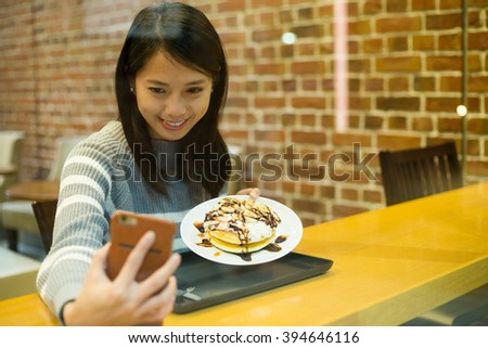 Woman take self photo with her dessert - stock photo