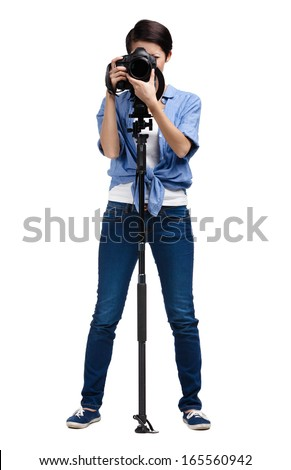 Woman takes snapshots holding photographic camera with monopod, isolated on white - stock photo