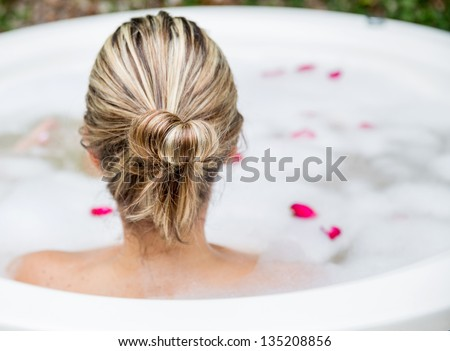 Woman taking a bubble bath - beauty concepts - stock photo